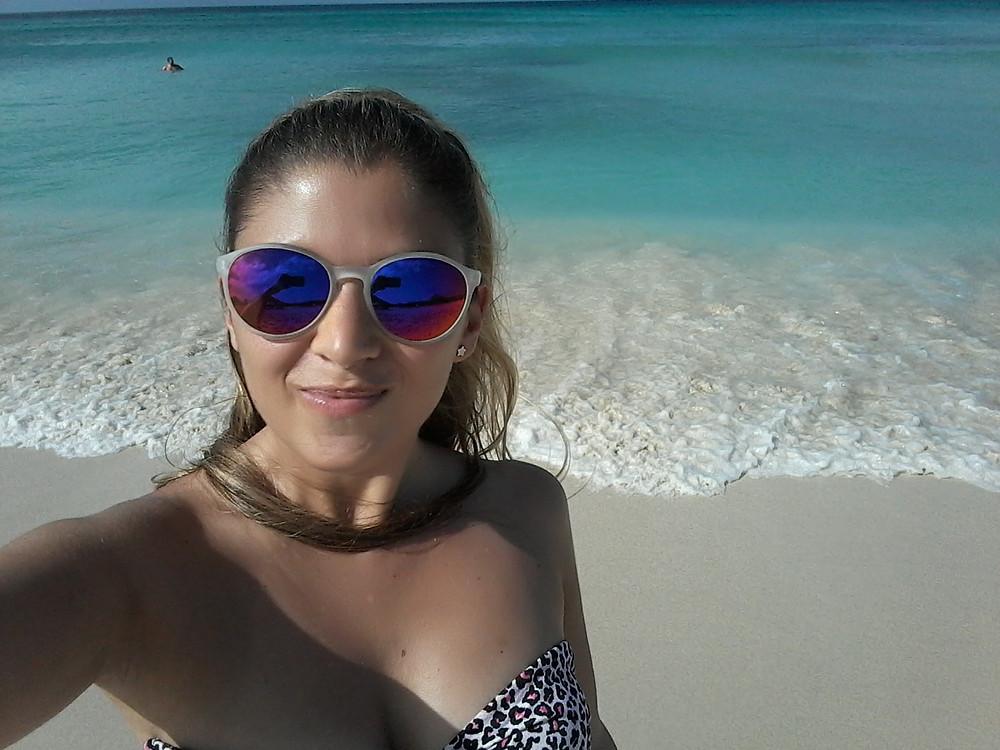 Mujer con lentes en playa - Aruba, Caribe - Playa con arena clara y el mar celeste