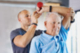 Physiotherapist helping senior perfrom home physiotherapy exercises