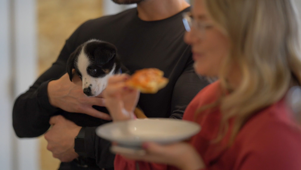 Man holding puppy standing beside women eating pizza