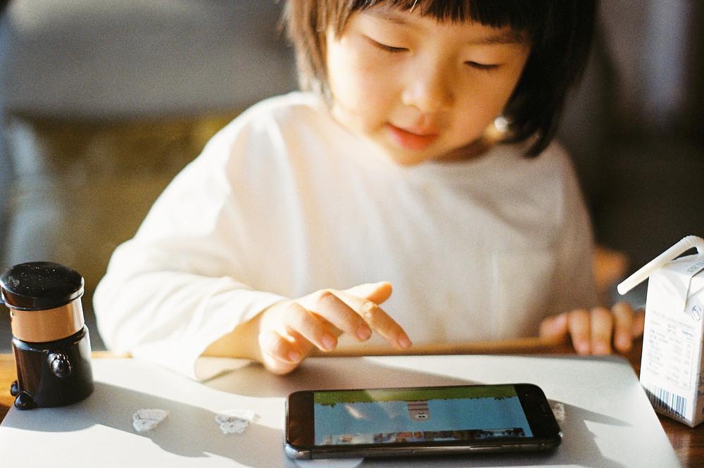 Uma criança brincando com smartphone