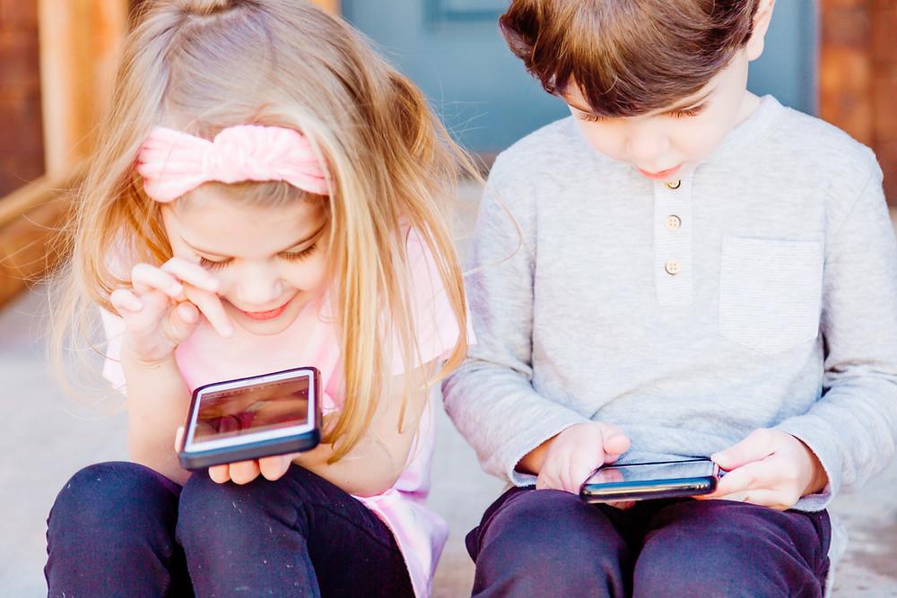 Duas crianças brincam em seus celulares smartphones