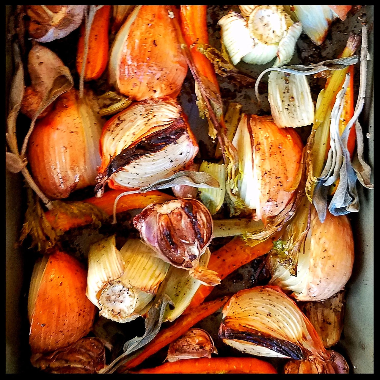 Roasted onions and carrots on baking sheet.