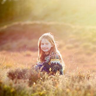 little girl sitting in long grass in soft evening light