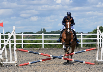 Chestnut horse and rider jumping a cross pole