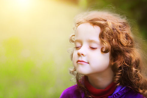 Little girl closed her eyes and breathes the fresh air in the park..jpg