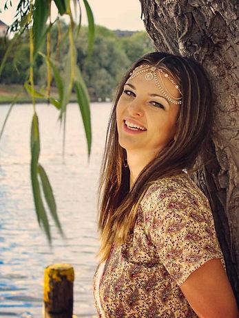 Milena Minuth an einem Baum mit einem See im Hintergrund