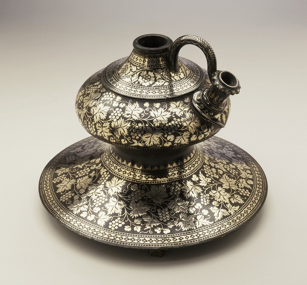 A zinc vessel with intricate designs on it made from silver