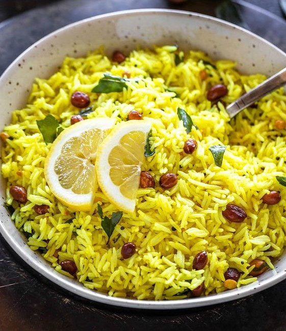 Yellow colored rice with peanuts and slices of lemon