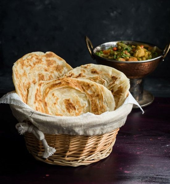 A basket containing paratha, a type of Indian Bread with a bowl of vegetables behind it