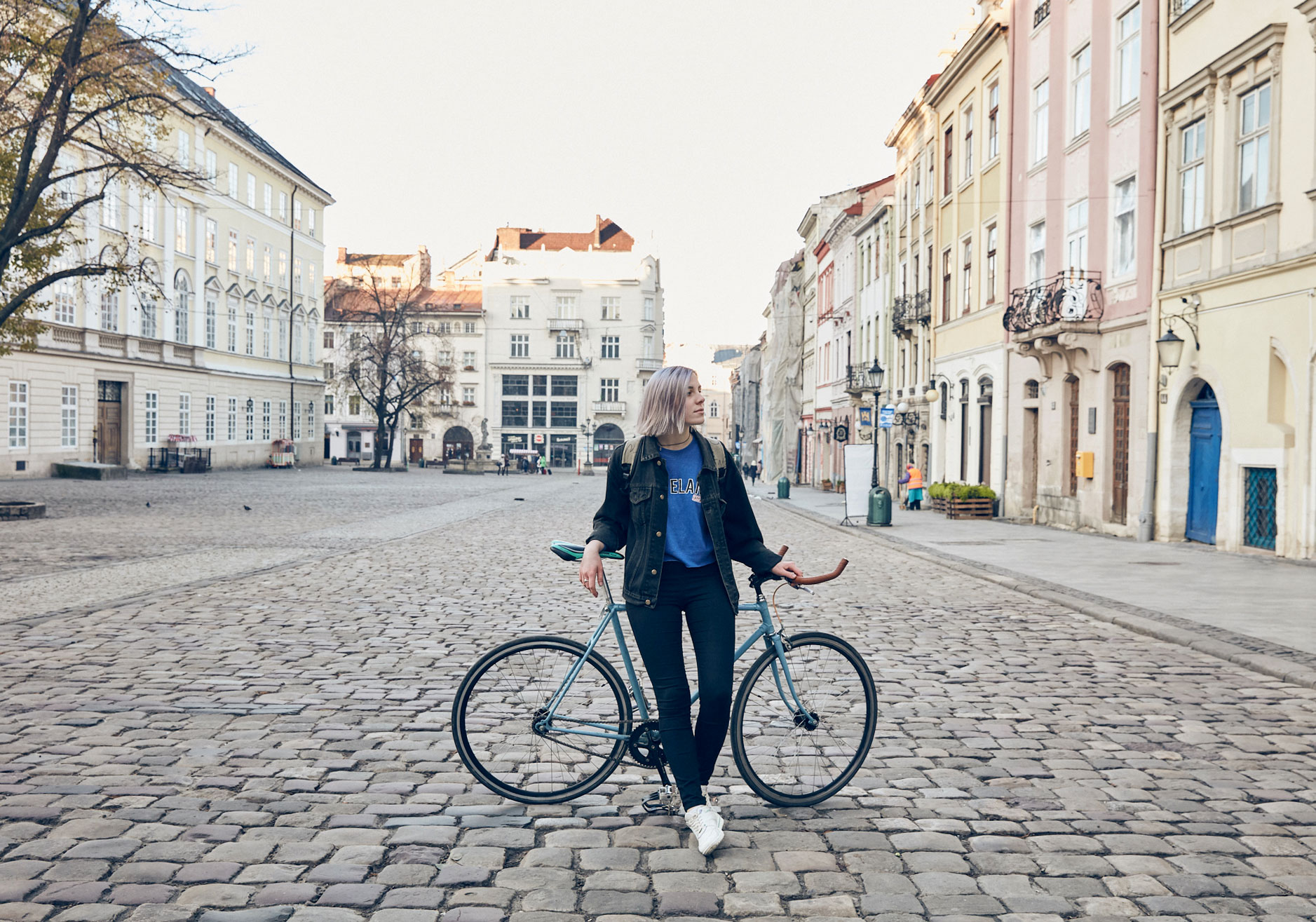 woman model posing in front of a bicycle in a town square