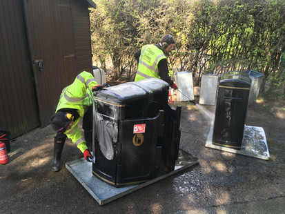 Pressure washing and cleaning the town's bins