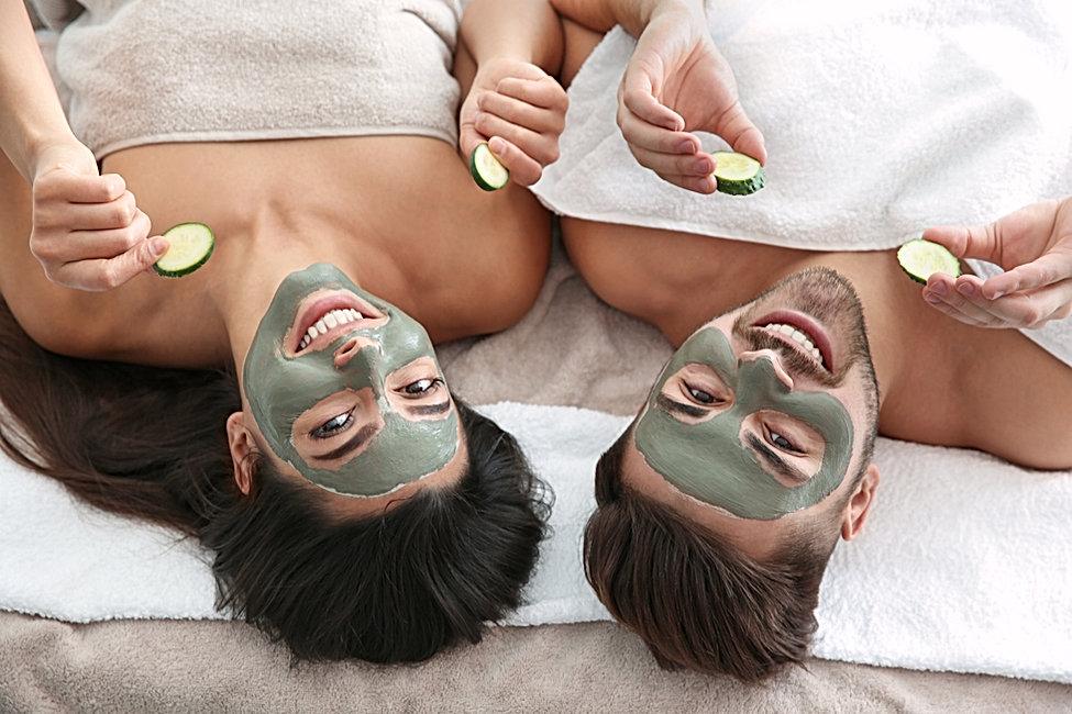 Happy couple enjoying facial treatment p