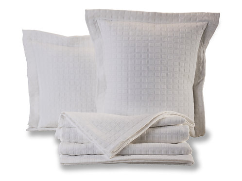 Folded Disley bedspread with cushion in white