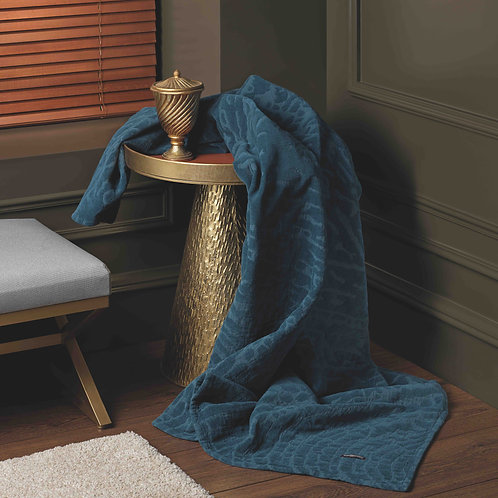 Image of Denzel bedspread in petrol colour draped over table