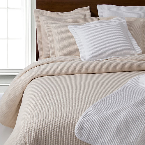 Neatly made bed showing Waffle in cream and white