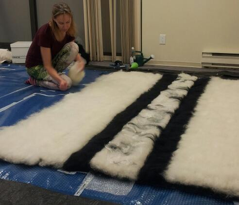 The process of making a large wall covering with only 2 hands.