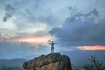 An inspiring person reaching goal of reaching top of mountain