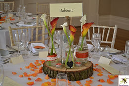 orange and ivory callas in bottles on wo