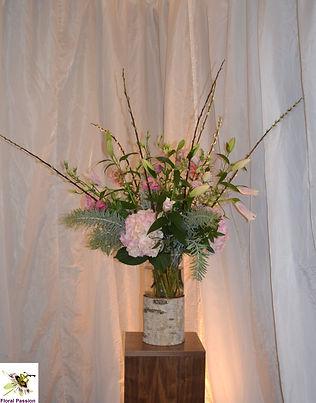 birch bark vase of pink flowers on woode