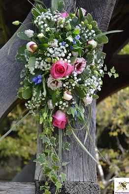 ceremony flower spray on woodern arbour.