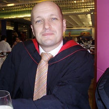 Bald man in a graduation gown