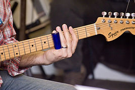 An electric guitar being played with a slide