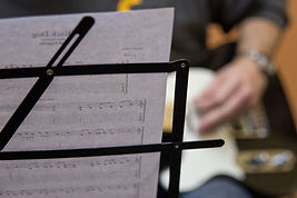 A sheet of music with a guitar player in the background
