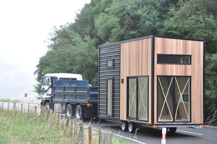 the ASTON Cube tiny house towed to location