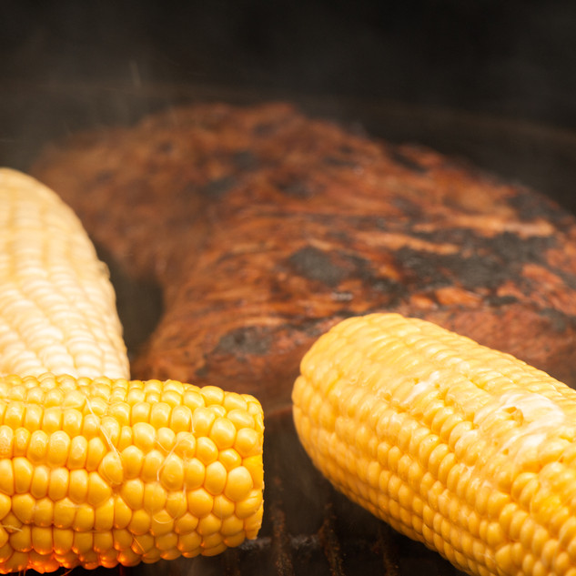 Tri-tip steak and corn on the cob being grilled on a Weber.