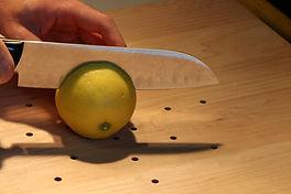 Knife cutting lemon on wood cutting boar