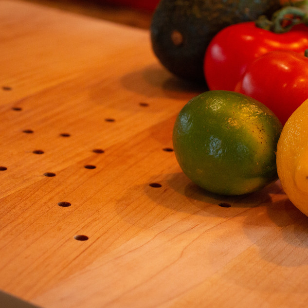 Limes, lemons, tomatos, and avacados on the Juice Catching Cutting Board.