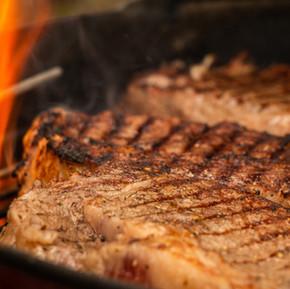 Grilled ribeye steak over flames.