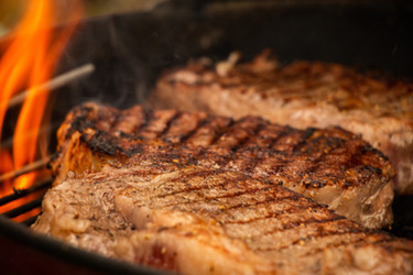 Ribeye steaks on a Weber grill, right before they are taken off for cutting on the Juice Catching Cutting Board.