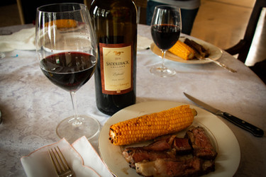 Ribeye Steak and Tri-tip Steak sliced on the Juice Catching Cutting Board and served with grilled corn and a delicious wine by Saddleback.