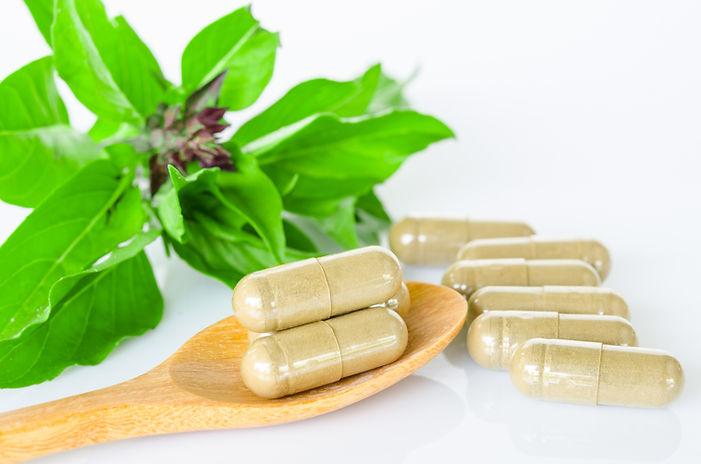 Herb capsule medicine in wooden spoon an