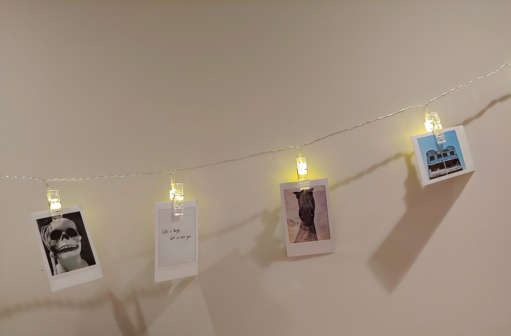 Lwind LED Photo Clip String Lights show a series of instagram photos hung on the wall