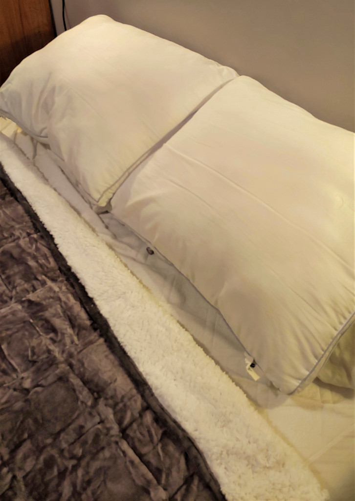 Sivio Sherpa Fleece Weighted Blanket shown on a bed with the fleecy underside visible