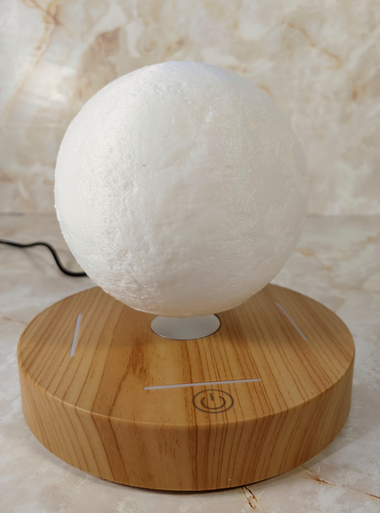 KFISI Moon Lamp floats above it's platform. Visible ridges dot the surface of the lamp