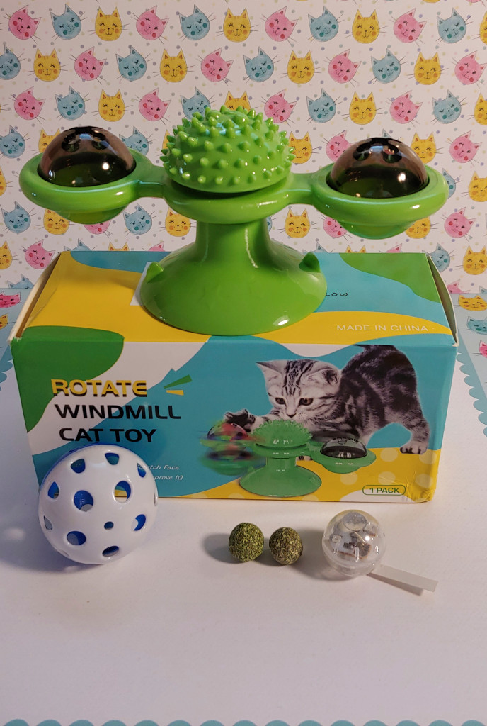 the rotating Cat Windmill Toy sits with it's packaging, two catnip balls and LED ball.