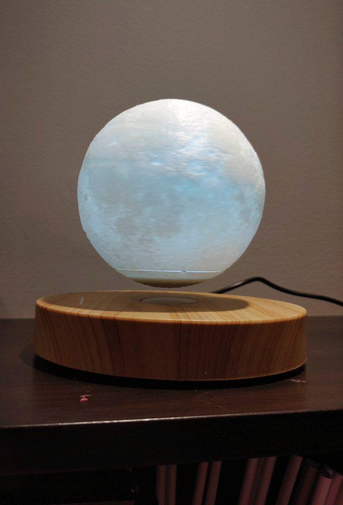 KFISI Moon Lamp levitates. A line and moon patterns can be seen on the light.