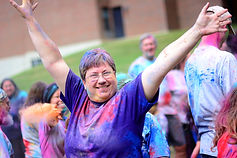 Woman with her hands in the air and paint in her hair. She is happy.