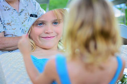 Girl holding a big circular mirror and looking at her enlarged reflection with a goofy smile.