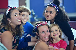 Kids and Young Adults with american flag bandanas hanging out and smiling.