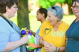 """Woman with grey hair wearing a yellow """"standing on the side of LOVE"""" shirt. She is laughing."""