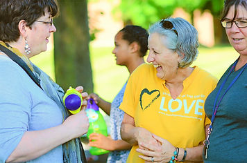 "Woman with grey hair wearing a yellow ""standing on the side of LOVE"" shirt. She is laughing."