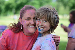 Mother and son smiling and covered in paint.