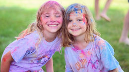 Two girls smiling with paint on their faces and in their hair. They are wearing colorful uumac shirts.