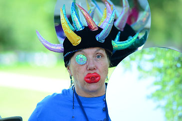 Woman in crazy, spiky, colorful hat with fake red lips at the UUMAC carnival.