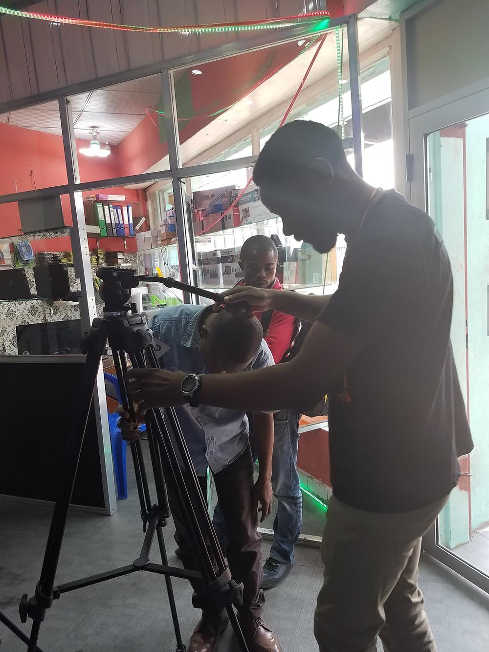 Tshoper Kabambi examines a tripod.