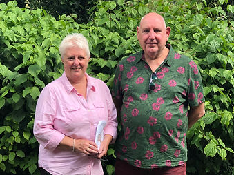 A husband and wife pet and house sitting team, living in Gloucestershire standing with a green hedge behind
